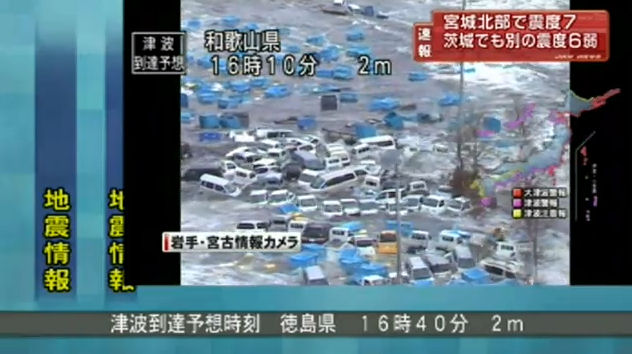 Cars being washed away by flood water from the tsunami.