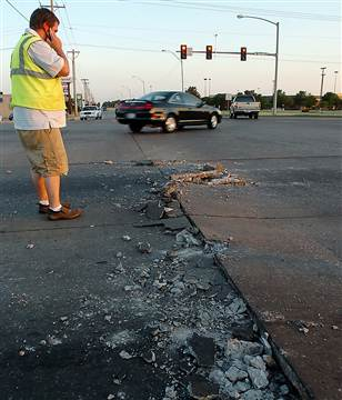 A road buckles under the oppressive heat in Oklahoma on a sweltering Saturday evening. Westbound lanes of U.S. 412 had to be shut down. (Credit: Billy Hefton / Enid News & Eagle via AP)