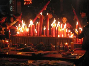 Chinese New Year celebrations include lighting candles and saying prayers to frighten away bad spirits.
