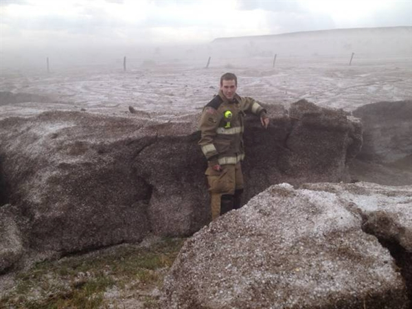A worker from Potter County Fire Department stands next to a boulder which is in fact a large collection of hail and ice.