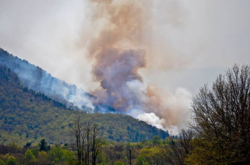 A photo from the National Park Service showing darker smoke indicating an increase in intensity and burning of denser hardwood fuels.